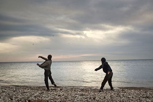 2012. Patras. Greece. Afghan boys throwing stones into the sea. They are waiting for evening, when they will try to sneak into the port, where they hope to illegally board a ship bound for Italy. Patras is one of the main escape points from Greece, due to the numerous cargo ships that dock in the port and are bound for Italy. It is therefore one of the points where it is possible to attempt to escape from Greece.
