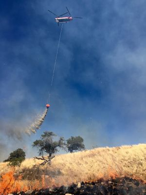 The Chinook helicopter dropping water on the edge of the fire to prevent its spread.